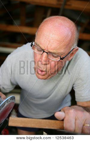 Old man sanding a wooden board