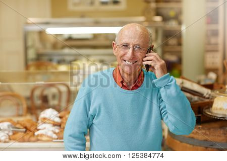 An elderly deli owner talking on the phone in his shop