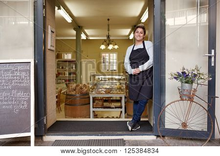 A young female deli employee standing in the doorway