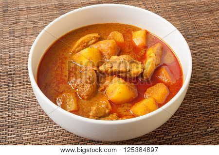 Spicy Thai red chicken curry called Massaman curry in white bowl sitting on bamboo mat