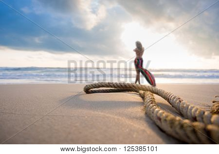 Woman on the beach and an old rope at sunrise focused on the rope
