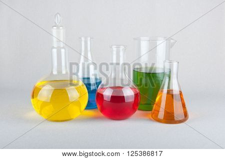 Chemical glasswares with yellow blue green red and orange liquid on white background