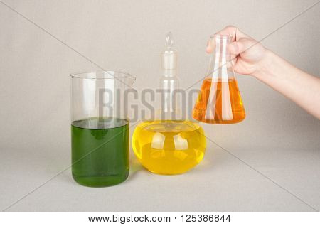 Laboratory bottles with yellow green and orange liquid on table. One glassware in hand. White background