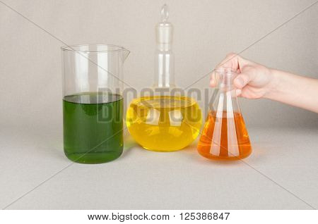 Three different forms laboratory glassware with colored liquid yellow green orange. One flask in hand. White background