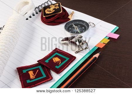 Orderliness White Scout Rope, Compass, Scouts Badge And Pencil On Wooden Table.