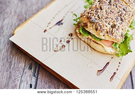 Cropped shot of fresh roll with whole frain seeds on top, filled with fresh sandwich ingredients and presented on brown paper on a wooden board