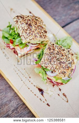High angle shot of a fresh sandwich made with seeded bread, with salami, tomato, chees and lettuce, presented on a rustic wooden board