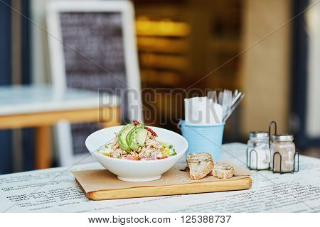 Fresh chcken and avacado sald in a presented in a bowl on a wooden board, alongside some freshly sliced bread laid out on a table outside a gourmet delicatessen eatery