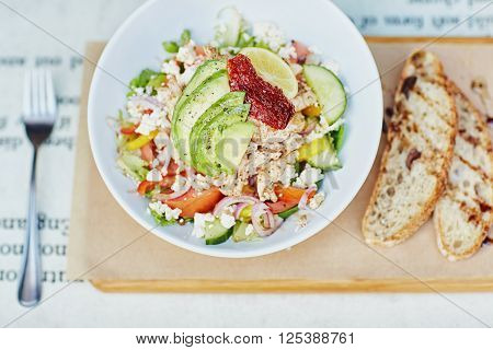 Overhead shot of a healthy chicken salad with fresh avocado and sundried tomato, presented on a rustic wooden board with slices of bread drizzled in balsamic vinegar