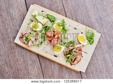 Overhead shot of a wooden platter with a fresh and healthy salad of tomato, chees, rocket and different kinds of ham, presented on a wooden table