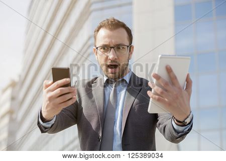 Young professional in suit holding smart phone and digital tablet device. He is under stress as of the huge amount of information he is receiving on daily basis.