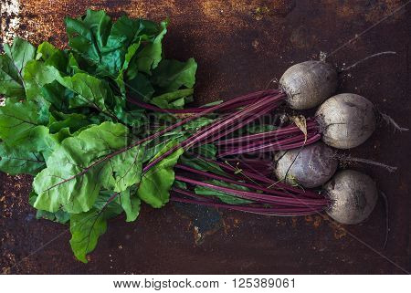 Bunch of fresh garden beetroot over grunge rusty metal backdrop, top view, horizontal