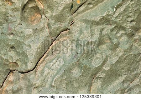 Abstract stone background texture photo of rock in green shade with fracture