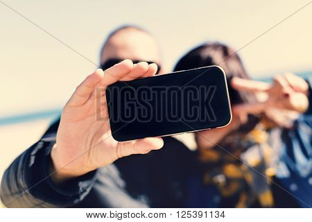closeup of a young man and a young woman taking a self-portrait with a smartphone while she is doing the victory sign, in front of the sea
