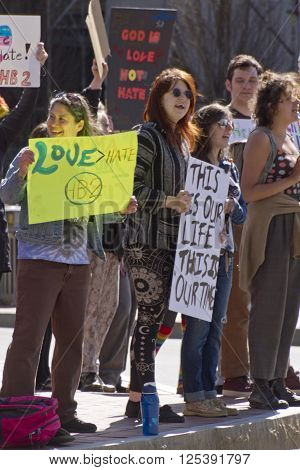 Asheville, North Carolina, USA - April 2, 2016: Crowd holds signs and protests the new North Carolina HB2 Law that restricts the rights of those who are gay or transgender