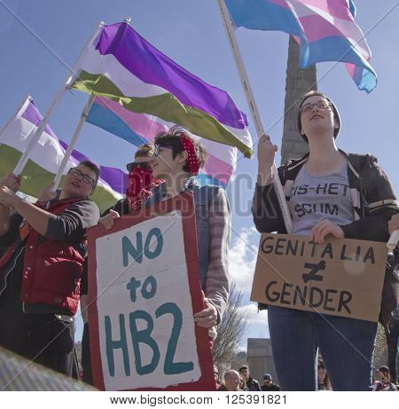 Asheville,North Carolina, USA - April 2, 2016: Crowd holds signs waves symbolic flags and protests the new North Carolina HB2 Law that restricts rights to those who are gay or transgender on April 2 2016 in downtown Ashevile NC