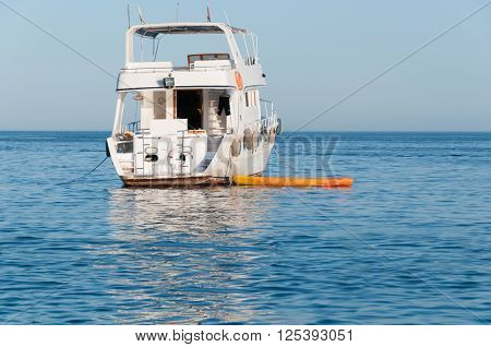 Kayak Tied To A Small Motor Yacht In A Tropical Sea