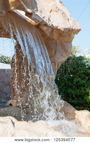 Artificial Waterfall In The Gardens Of A Luxury Resort Hotel