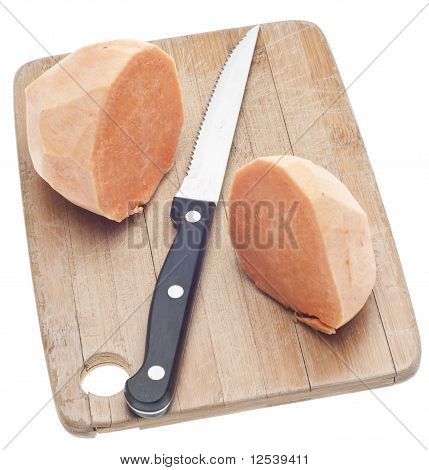 Sliced Sweet Potatoes On A Wooden Chopping Block