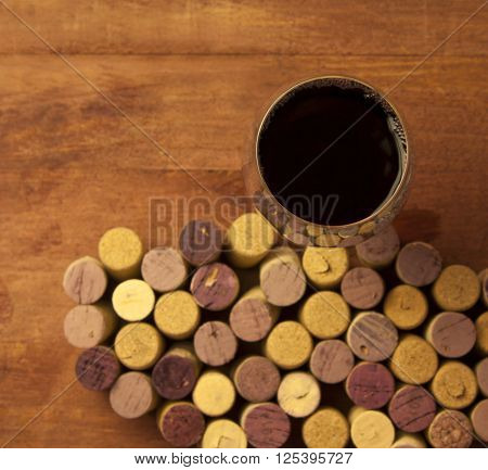 A glass of dark red wine shot from above on a blurred wooden background with defocused wine corks from white and red wine forming a pattern ** Note: Shallow depth of field