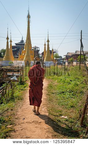 Burmese Buddhist monk walks along a dirt path toward the gold painted stupas of a temple in Myanmar.
