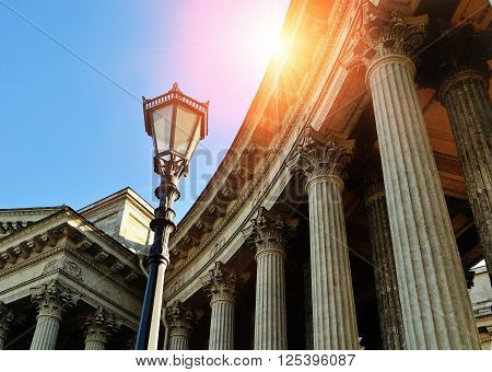 Elements of architectural ensemble of Kazan Cathedral in Saint Petersburg Russia - colonnade and metal lantern under shining sunset light