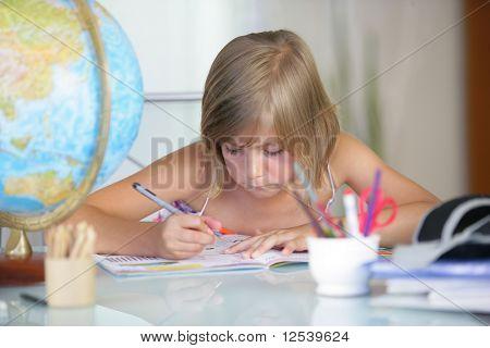 Portrait of a little girl doing homework