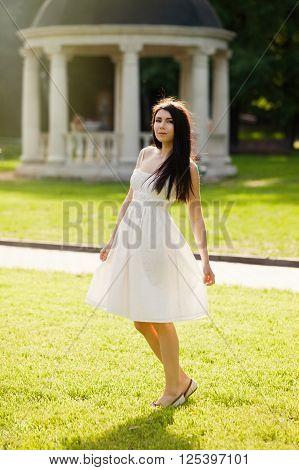 Young Brunette Girl In Sundress Posing Outdoors