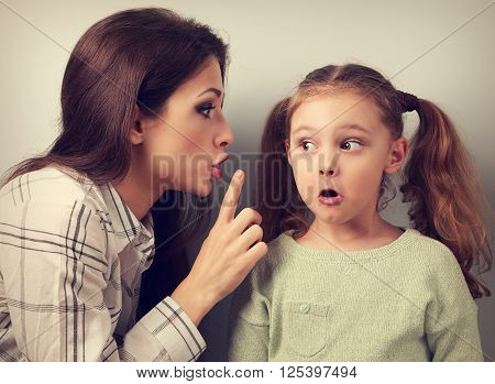 Young Mother Showing The Finger The Silence Sign To Her Surprising Daughter And Talking