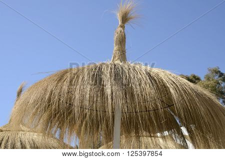 Straw sun shade on the beach of Marbella Spain.