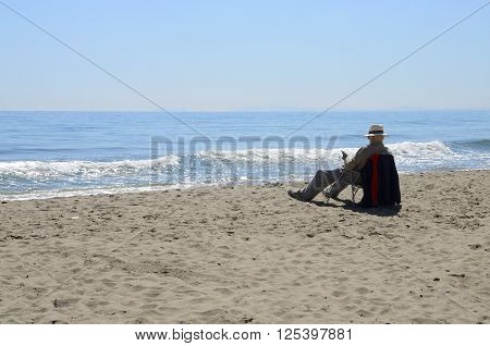 MARBELLA, SPAIN - APRIL 9, 2016: Man reading at the shore of the sea in Marbella Spain. ** Note: Soft Focus at 100%, best at smaller sizes