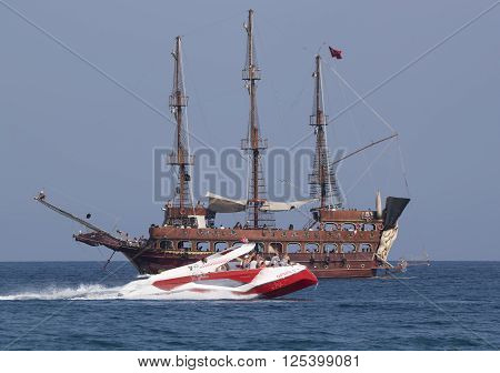 CAMYUVA KEMER TURKEY - JULY 11 2015: On the coast of Turkey widespread various marine activities. Among them flyboard walks on boats and yachts stylized pirate schooner