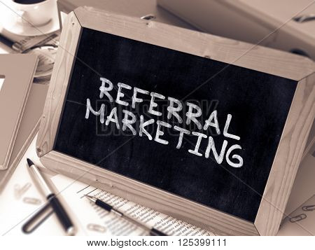 Referral Marketing Handwritten on Chalkboard. Composition with Small Chalkboard on Background of Working Table with Office Folders, Stationery, Reports. Blurred, Toned Image. 3D Render.