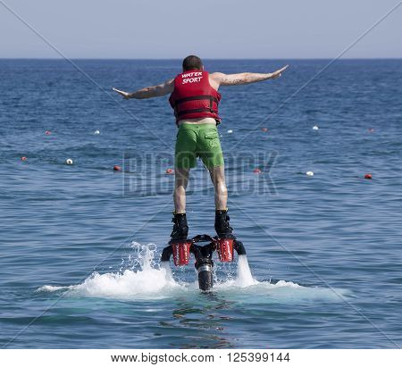 CAMYUVA KEMER TURKEY - JULY 16 2015: Unidentified Turkish man studying extreme flyboard. Extreme water sports are increasingly popular on the beaches of Turkey