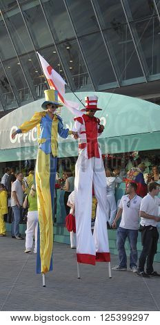 DONETSK UKRAINE - JUNE 19 2012: Unidentified Ukrainian and English soccer fans in the colors of the national flag on stilts before UEFA EURO 2012 match in Donetsk on Donbass Arena