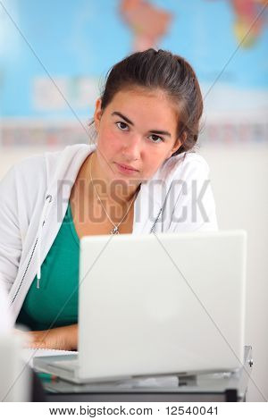Portrait of a young girl in classroom with a laptop computer
