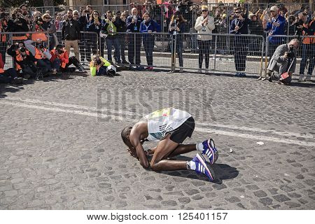 Rome Italy - April 10 2016: Amos Kipruto immediately after the line in Via dei Fori Imperiali kneels before the public and photographers and kiss the asphalt in gratitude for the achieved results.