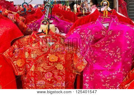 Chinese style red silk dresses for sale in a shop in Bangkok Thailand traditionally worn to welcome the Lunar New Year.