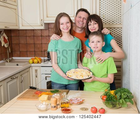 Mother father and children holding prepared raw pizza in the kitchen. Happy family cooking pizza at home. Filling homemade pizza with ingredients.