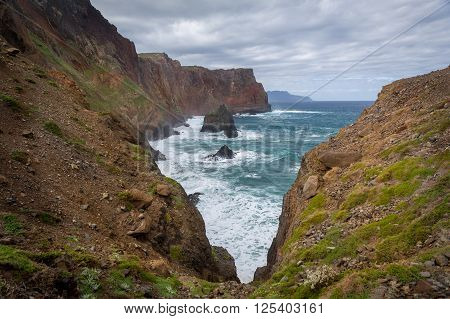 Dangerous cliff on the hiking path to the eastern cape.  Madeira island rocky coast, Portugal.
