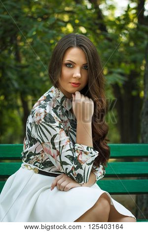 Beautiful brunette girl poses and relaxed on bench outdoors