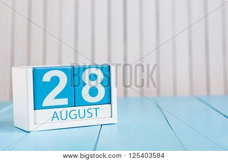 August 28th. Image of august 28 wooden color calendar on blue background. Summer day. Empty space for text.