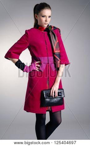 fashion model in fashion red dress holding handbag posing in light background