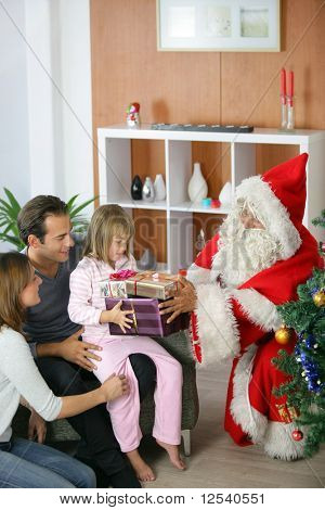 Santa Claus giving presents to a little girl with her parents
