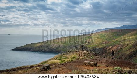 Panoramic view of Madeira east tail coast. Some tourists with backpacks walking on hiking path and looking at beauty of nature. Madeira island, Portugal.