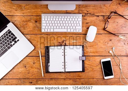 Desk with gadgets and office supplies. Computer keyboard, notebook, personal organizer, smart phone and stationery around the workplace. Flat lay.