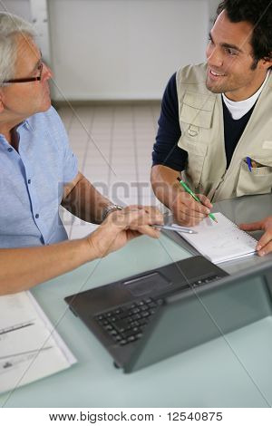 Portrait of a two men in front of a laptop computer and writing on a pad