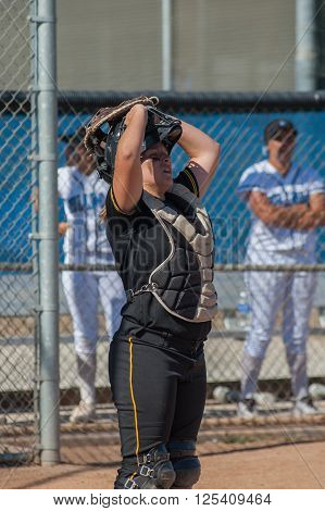 Strong softball player in black uniform lifting her mask between plays.