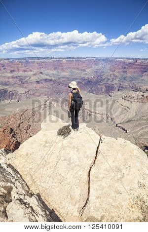 Young Woman Standing On The Edge Of A Cliff And Taking Pictures.