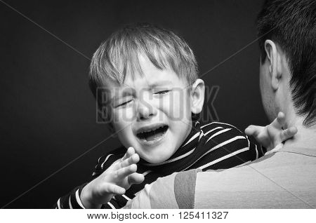 Portrait of a crying son on hands a father